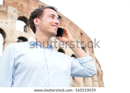 Business man on cell phone, Colosseum, Rome, Italy. Young businessman talking on smartphone outside smiling happy in casual shirt in front of Coliseum. Caucasian male professional in Europe. - stock photo