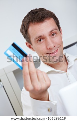 Business man on laptop showing credit card in his office - stock photo
