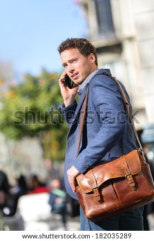 Business man on smartphone walking in street talking on mobile smart phone smiling wearing jacket and leather laptop bag on Passeig de Gracia, Barcelona, Catalonia, Spain. - stock photo