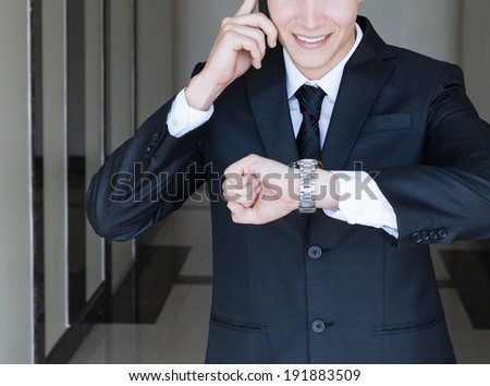 Business man on the phone while checking the time on his wrist watch.
