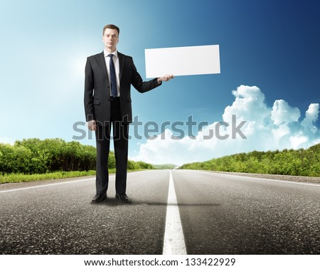 business man on the road whith blank in hand - stock photo