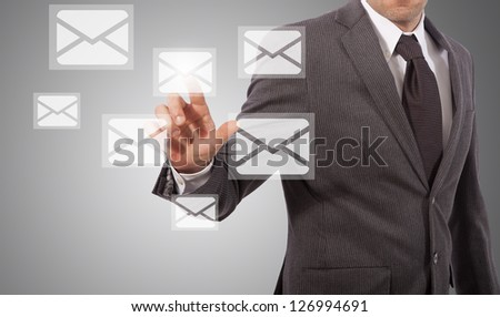 business man open email touching icon on screen, grey background - stock photo