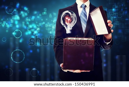 Business man opening box with an idea light bulb on blue technology background - stock photo
