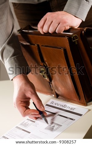 Business man opening elegant brown leather briefcase and showing printed business report. - stock photo