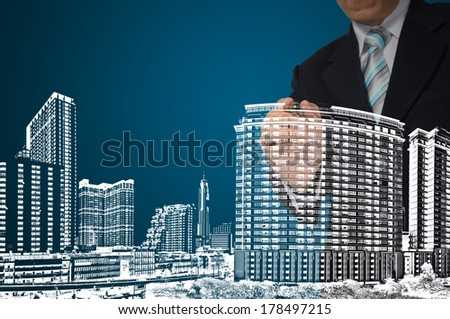 Business man or architect draw building and cityscape on blue background - stock photo