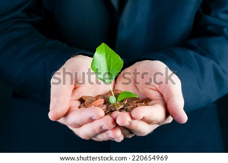 Business man or manager in suit holding seedling in his hands. the  soil is made of coins - stock photo
