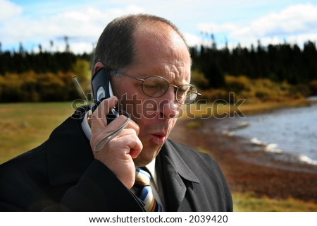 Business man outdoors on phone - stock photo