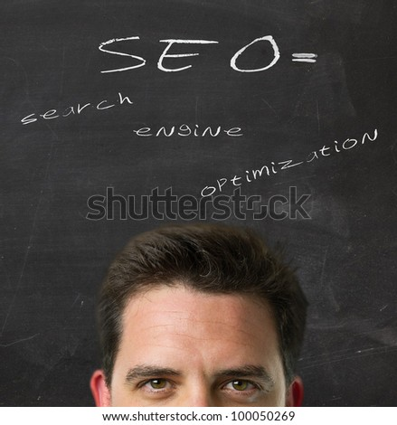 Business man over blackboard with the explanation of the acronym SEO - stock photo