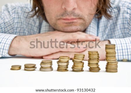 Business man over coin stack thinking about possible money investments. - stock photo