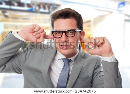 Business man over shopping center background. Tapping his ears with his fingers - stock photo