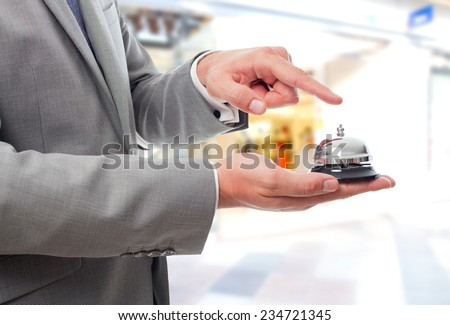 Business man over shopping center background. Using a hotel bell