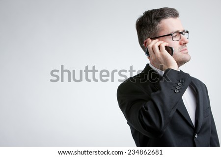 business man phoning with a mobile and looking elsewhere but in the COPY SPACE area - stock photo