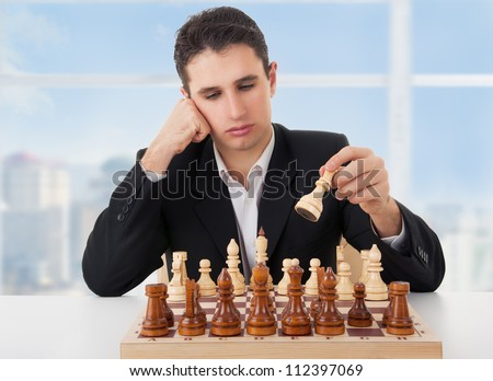 business man playing chess, making the first move - stock photo