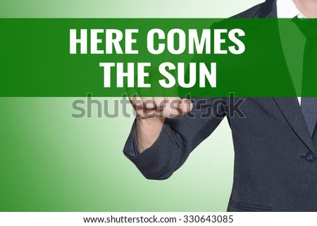 Business man point to Here Comes the Sun word on green tab virtual screen - stock photo