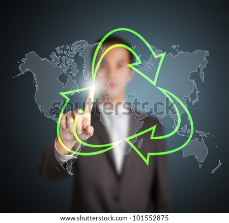 business man pointing at green recycle symbol with world map background - stock photo