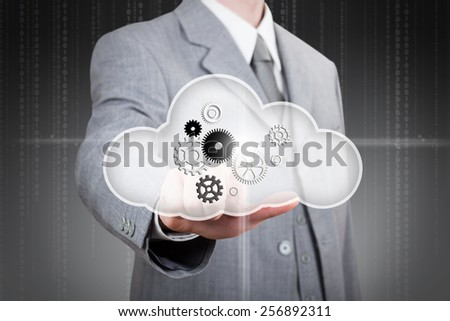 business man pointing at set of gears in the cloud - stock photo