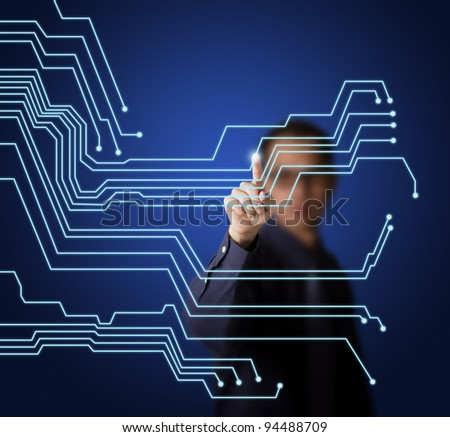 business man pointing at virtual electronic circuit board on touchscreen - stock photo