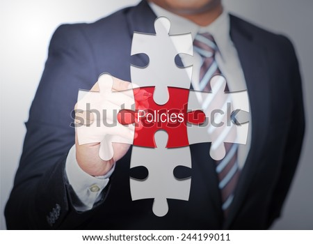 Business Man pointing on jigsaw written word Policies - stock photo