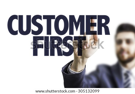 Business man pointing the text: Customer First - stock photo