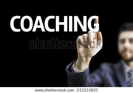 Business man pointing to black board with text: Coaching  - stock photo