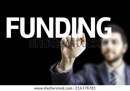 Business man pointing to black board with text: Funding - stock photo