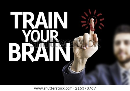 Business man pointing to black board with text: Train your Brain - stock photo