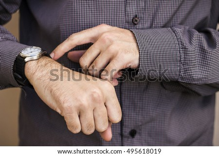 business man pointing to the wristwatch