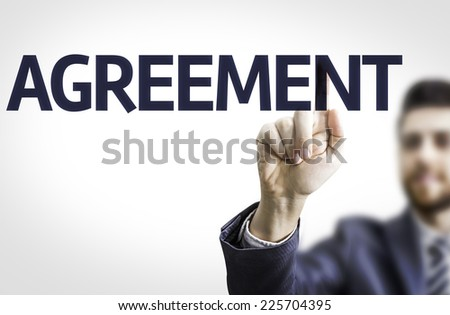 Business man pointing to transparent board with text: Agreement - stock photo