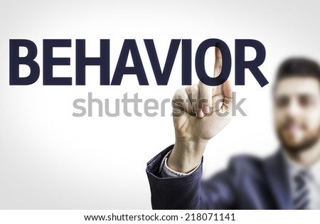 Business man pointing to transparent board with text: Behavior - stock photo