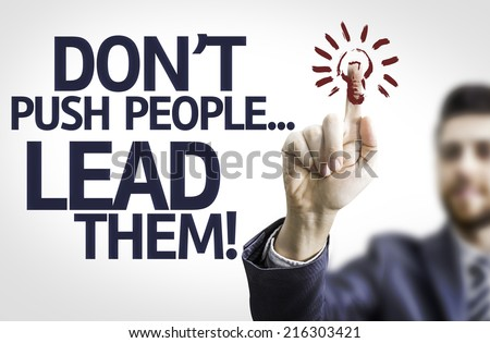 Business man pointing to transparent board with text: Don't Push People...Lead Them! - stock photo