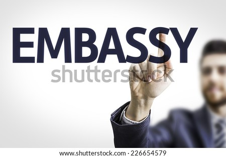 Business man pointing to transparent board with text: Embassy - stock photo