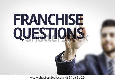 Business man pointing to transparent board with text: Franchise Questions  - stock photo