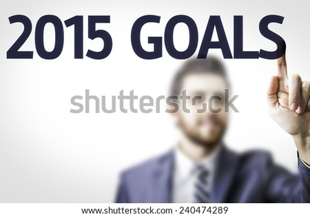 Business man pointing to transparent board with text: 2015 Goals - stock photo