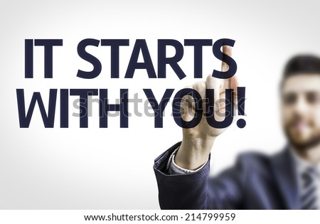 Business man pointing to transparent board with text: It Starts with You!  - stock photo