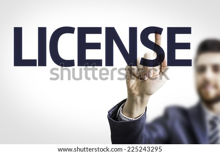 Business man pointing to transparent board with text: License - stock photo