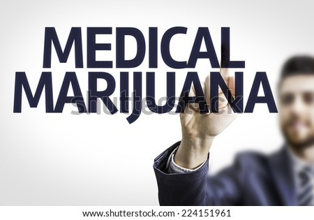 Business man pointing to transparent board with text: Medical Marijuana - stock photo