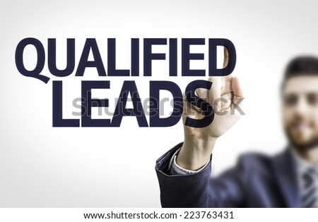 Business man pointing to transparent board with text: Qualified Leads - stock photo