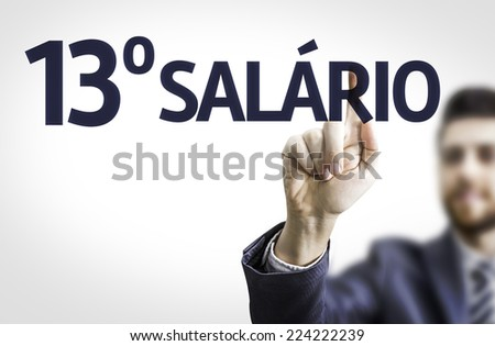 Business man pointing to transparent board with text: 13 Salary (In Portuguese)  - stock photo