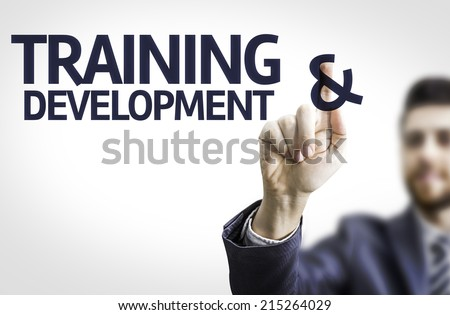 Business man pointing to transparent board with text: Training & Development - stock photo