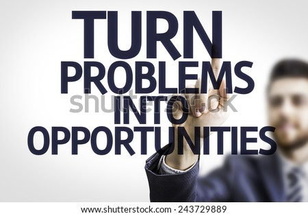 Business man pointing to transparent board with text: Turn Problems into Opportunities - stock photo