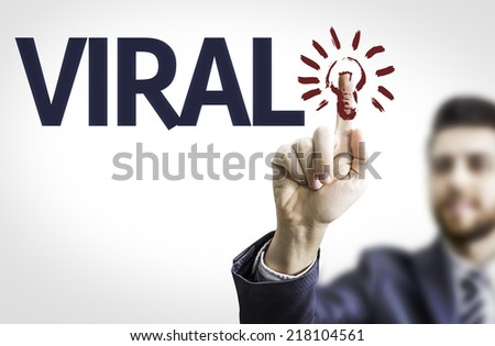 Business man pointing to transparent board with text: Viral - stock photo