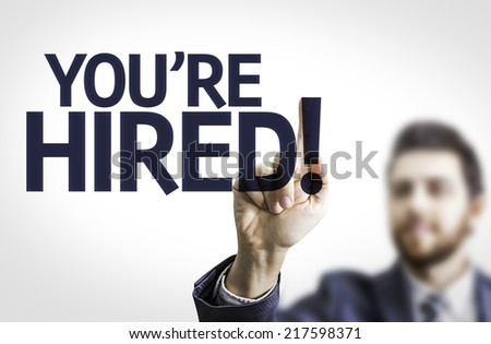 Business man pointing to transparent board with text: You're Hired! - stock photo
