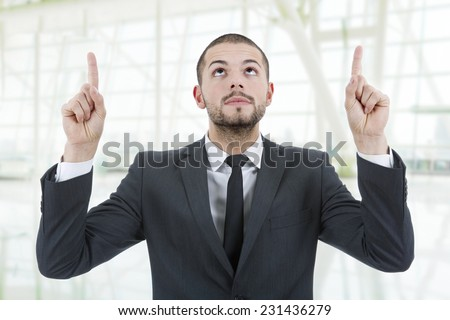 business man pointing up with his fingers at the office - stock photo