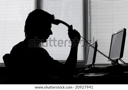 Business man pondering over the phone, in back light - stock photo
