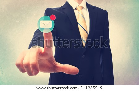 Business man pressing an email button on a blurred neutral background - stock photo