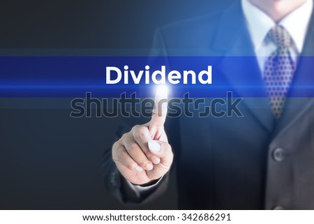 Business man pressing hand Dividend word on virtual screen - stock photo