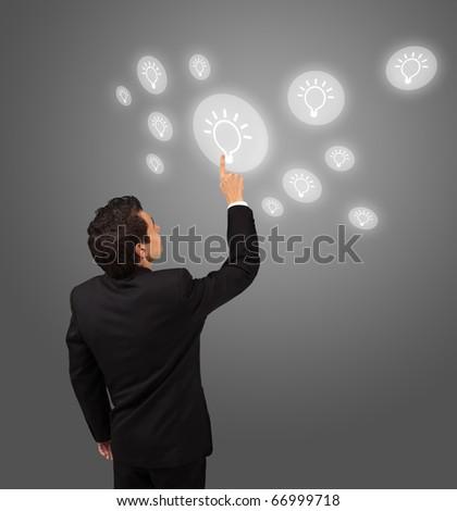 business man pressing lightbulp button - stock photo