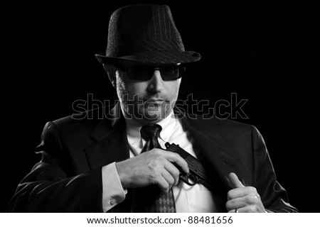 Business man pulling a gun from his suit coat.