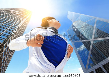 Business man pulling his t-shirt open, showing superhero suit with city building background, asian, hong kong - stock photo