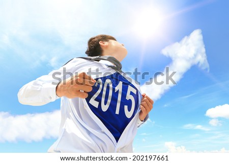 Business man pulling his t-shirt open, showing 2015 text with a superhero suit underneath his suit - stock photo